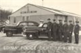 Historic photo of police officers lined up by car