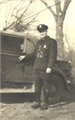Historic photo of police officer by police car