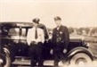 Two Police Officers in front of car