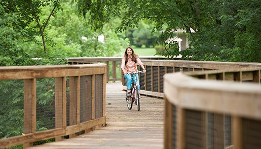 Beth Reissenweber riding her bike on a bridge