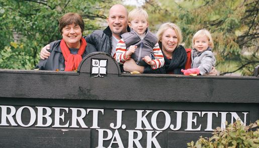 Bradley Smith posing with his family behind the Robert J. Kojetin Park sign