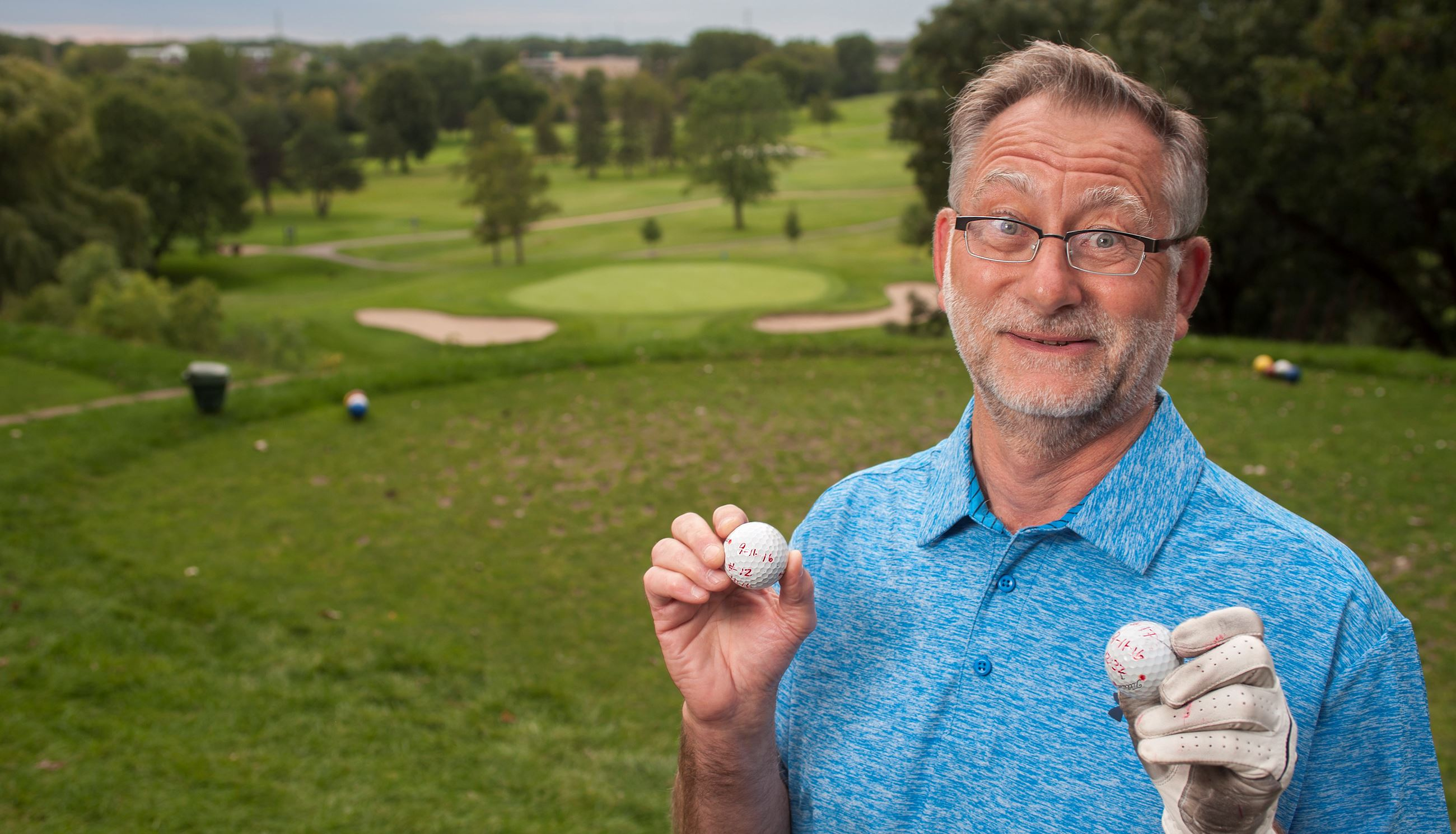 Michael Zamyslowski holding his 2-hole-in-one golf balls