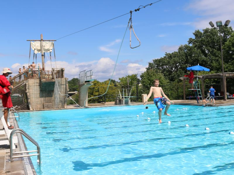 Kid on zip line over main pool