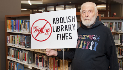 Sanford Berman holds sign saying Abolish Library Fines