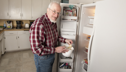 Hometown Hero Bruce Kieffer stands in his kitchen container he uses for organics recycling